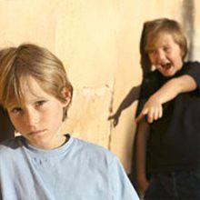 boy in black shirt bullying boy in gray shirt